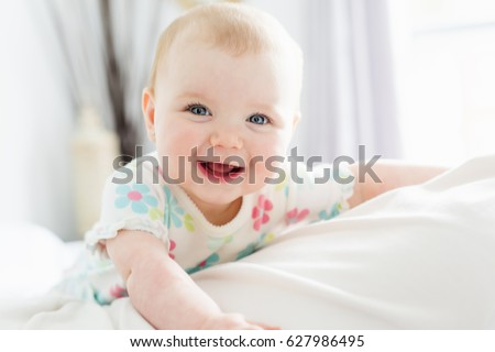A Baby girl in white bedding at home look nice