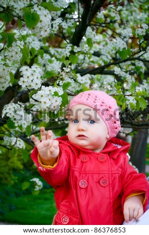 a baby girl is in the garden next to the blossom tree in spring