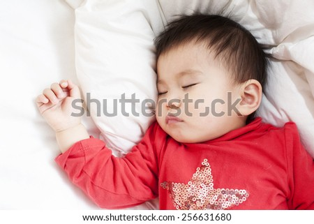 A baby girl is sleeping in red shirt, on a white bed sheet and blanket, on a white pillow, right hand making a fist, closeup