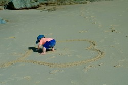 A baby in blue shorts and a heart drawn on the sand on the beach. Image selective fokus. Focus on the baby. Image with toning