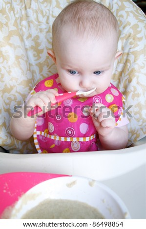 a baby is eating her cereal
