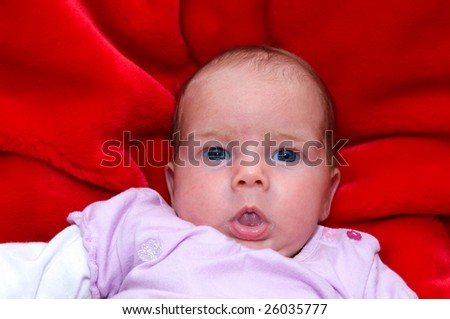 A baby on a red pillow