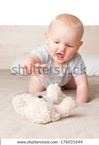 A baby on his knees enjoying his fluffy toy.