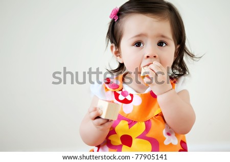 A baby putting child blocks into her mouth with copyspace