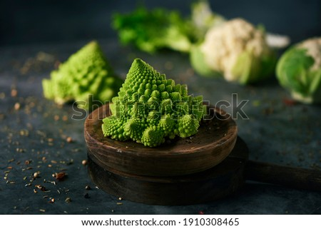 a baby romanesco broccoli head on a wooden plate, placed on a dark stone surface next to some another baby romanesco broccoli head and some baby cauliflower heads Foto d'archivio ©
