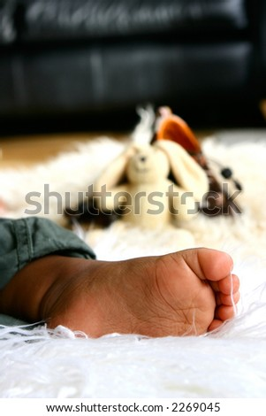 A baby\'s foot as he lays asleep on sheep skin rug with some baby toys in background.