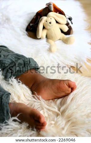 A baby's foot as he lays asleep on sheep skin rug with some baby toys in background.