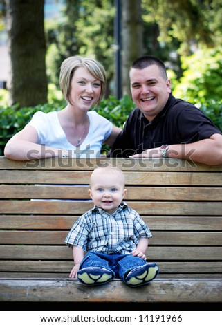 A baby sitting on a park bench while his parents are seated behind him smiling.
