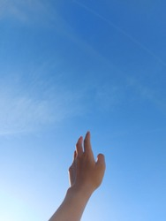a back hand with beautiful clear blue sky in the background symbolizes a person that reaching a dream as high as the sky
