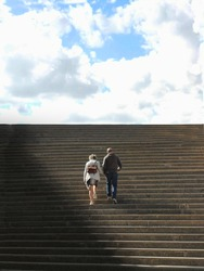 A back view of a lovely senior couple ascending wide long stairs to the cloudy sky