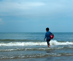 A back view of a Thai young boy wearing a blue top and a pair of denim shorts.  He is carrying a pink plastic ball and black pattern.   He plays sea waves on the beach of Chonburi in Thailand.