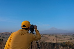 A back view of a young Mexican professional photographer with a camera capturing the beautiful landscape