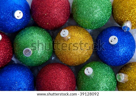 A background comprised of blue, green, red and gold glittery Christmas ornaments