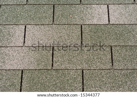 A background of large roof shingles with red and white pebbles