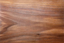 A background of the rich,  brown, figured and textured wood grain of a plank of Walnut.