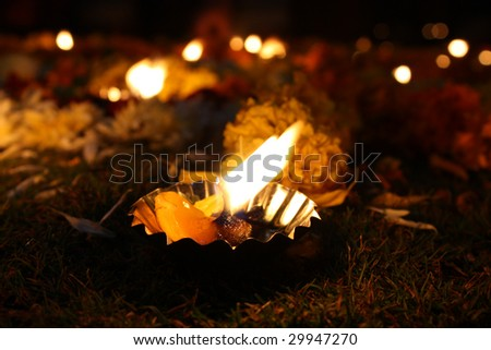 A background with a closeup view of a beautiful lamp lit near traditional flower decoration during Diwali festival in India.