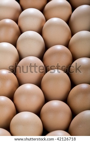 A background with lots of brown chicken eggs, from above.