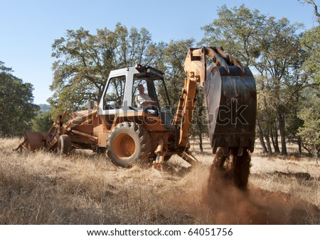 A backhoe digging up some dirt holes in the ground.