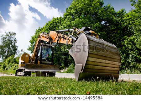 A backhoe sitting on grass