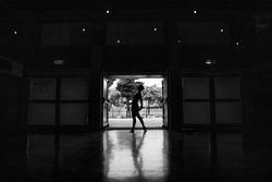 A backlit black and white shot of a ballerina during practice