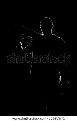 A backlit skateboarder guy posing under dramatic rear rim lighting with his skateboard in black and white.
