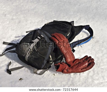 A backpack with water and red ski gloves in the snow.