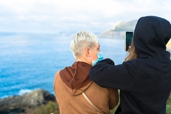 A backshot of two females taking pictures of scenic waterscape