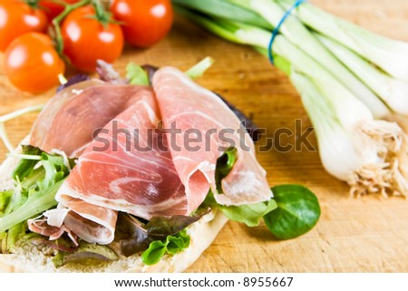 A bagel sandwich with parma ham, spring onions and tomatoes