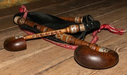 A bagpipe is a traditional musical instrument lying on a wooden floor. Close-up.