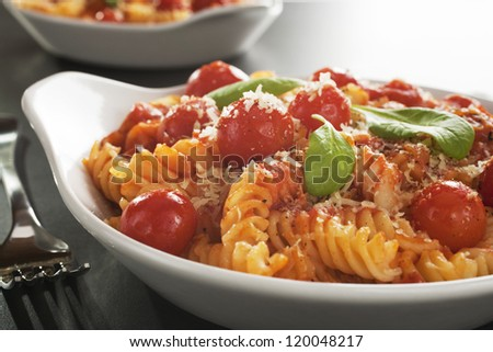A baked dish of fusilli or pasta spirals, with cherry tomatoes, ricotta and parmesan.