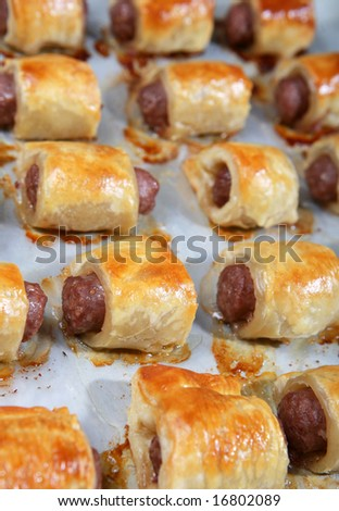 A baking tray of freshly cooked sausage rolls.