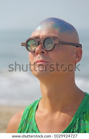 A bald and unusual young man, a freak, with a shiny bald head and round wooden glasses on the background of the beach and the sea. Humor and eccentricity. Unusual appearance. Humorist. #1029924727