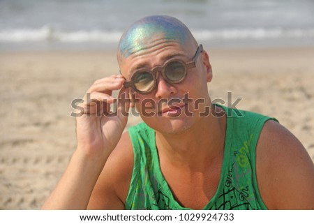 A bald and unusual young man, a freak, with a shiny bald head and round wooden glasses on the background of the beach and the sea. Humor and eccentricity. Unusual appearance. Humorist. #1029924733