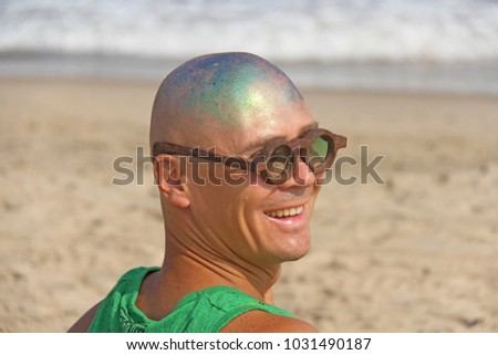 A bald and unusual young man, a freak, with a shiny bald head and round wooden glasses on the background of the beach and the sea. Humor and eccentricity. Unusual appearance. Humorist. #1031490187