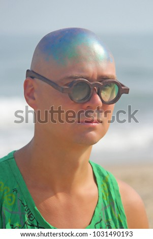 A bald and unusual young man, a freak, with a shiny bald head and round wooden glasses on the background of the beach and the sea. Humor and eccentricity. Unusual appearance. Humorist. #1031490193