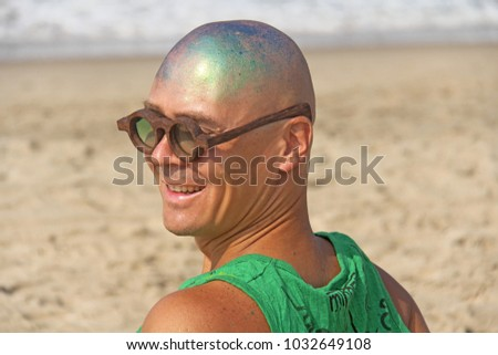 A bald and unusual young man, a freak, with a shiny bald head and round wooden glasses on the background of the beach and the sea. Humor and eccentricity. Unusual appearance. Humorist. #1032649108