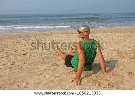 A bald and unusual young man, a freak, with a shiny bald head and round wooden glasses on the background of the beach and the sea. Humor and eccentricity. Unusual appearance. Humorist. #1050213035