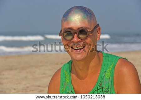 A bald and unusual young man, a freak, with a shiny bald head and round wooden glasses on the background of the beach and the sea. Humor and eccentricity. Unusual appearance. Humorist. #1050213038