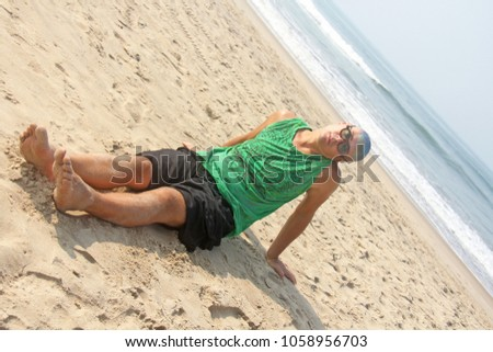 A bald and unusual young man, a freak, with a shiny bald head and round wooden glasses on the background of the beach and the sea. Humor and eccentricity. Unusual appearance. Humorist. #1058956703