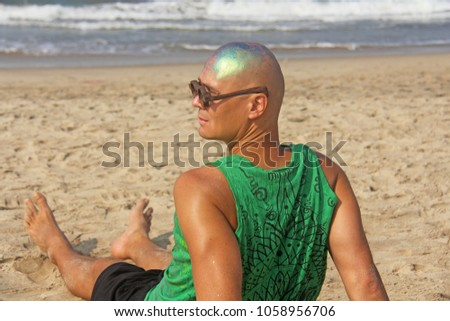 A bald and unusual young man, a freak, with a shiny bald head and round wooden glasses on the background of the beach and the sea. Humor and eccentricity. Unusual appearance. Humorist. #1058956706