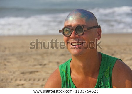 A bald and unusual young man, a freak, with a shiny bald head and round wooden glasses on the background of the beach and the sea. Humor and eccentricity. Unusual appearance. Humorist. #1133764523