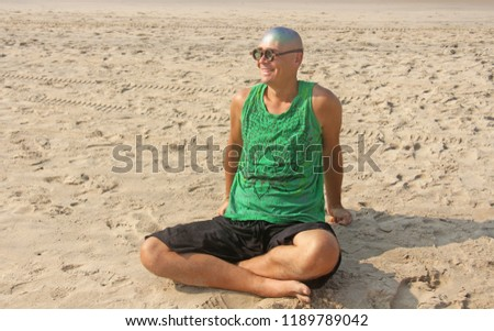 A bald and unusual young man, a freak, with a shiny bald head and round wooden glasses on the background of the beach and the sea. Humor and eccentricity. Unusual appearance. Humorist. #1189789042