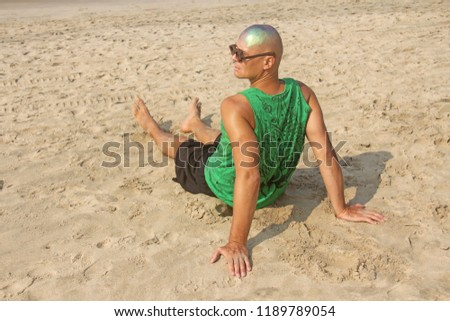 A bald and unusual young man, a freak, with a shiny bald head and round wooden glasses on the background of the beach and the sea. Humor and eccentricity. Unusual appearance. Humorist. #1189789054