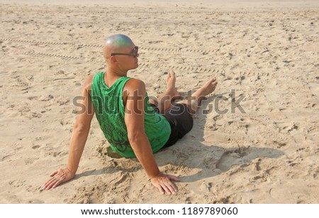 A bald and unusual young man, a freak, with a shiny bald head and round wooden glasses on the background of the beach and the sea. Humor and eccentricity. Unusual appearance. Humorist. #1189789060