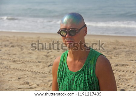 A bald and unusual young man, a freak, with a shiny bald head and round wooden glasses on the background of the beach and the sea. Humor and eccentricity. Unusual appearance. Humorist. #1191217435