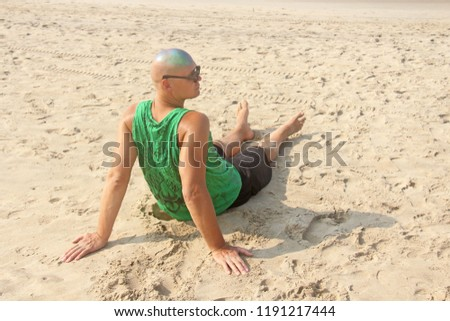 A bald and unusual young man, a freak, with a shiny bald head and round wooden glasses on the background of the beach and the sea. Humor and eccentricity. Unusual appearance. Humorist. #1191217444