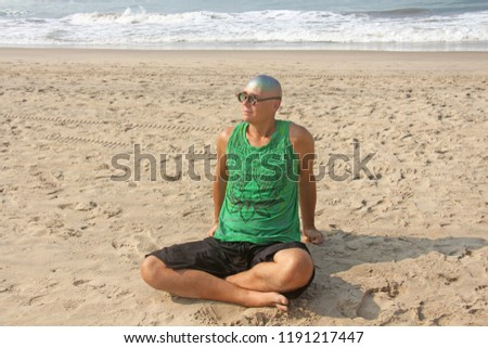 A bald and unusual young man, a freak, with a shiny bald head and round wooden glasses on the background of the beach and the sea. Humor and eccentricity. Unusual appearance. Humorist. #1191217447