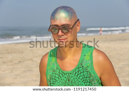 A bald and unusual young man, a freak, with a shiny bald head and round wooden glasses on the background of the beach and the sea. Humor and eccentricity. Unusual appearance. Humorist. #1191217450