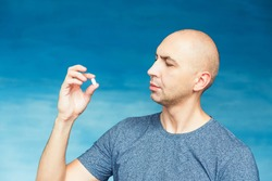 A bald man eats pills on the blue background.