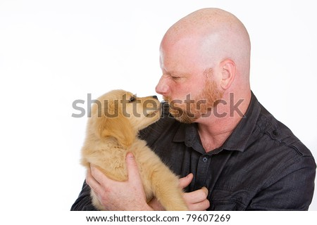 a bald man holding a golden retriever puppy.